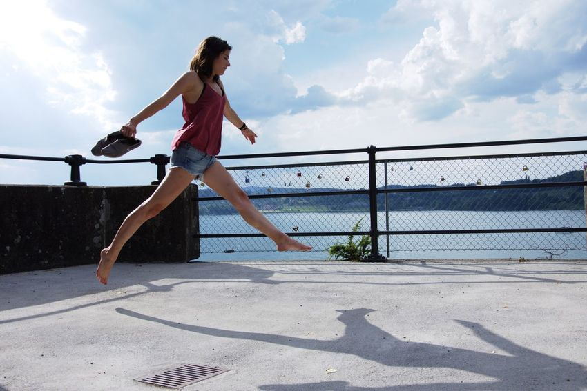 EyeEm Selects Sky Full Length Outdoors Day Railing Sunlight Real People Cloud - Sky Water Balance Leisure Activity Lifestyles Mid-air Casual Clothing Jumping Shadow Fun Sea One Person Young Women