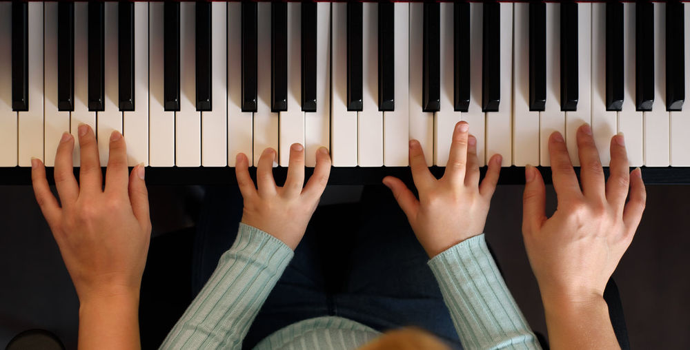 Cropped hand of mother and daughter playing piano at home