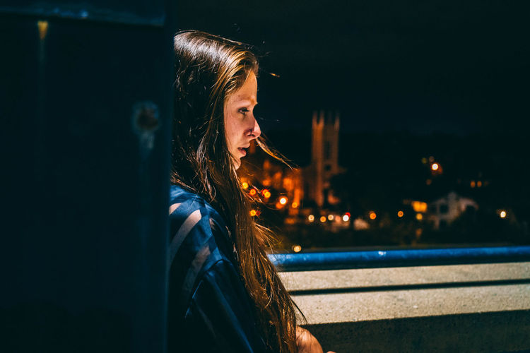 Side View Of Sad Thoughtful Woman Looking Away At Night