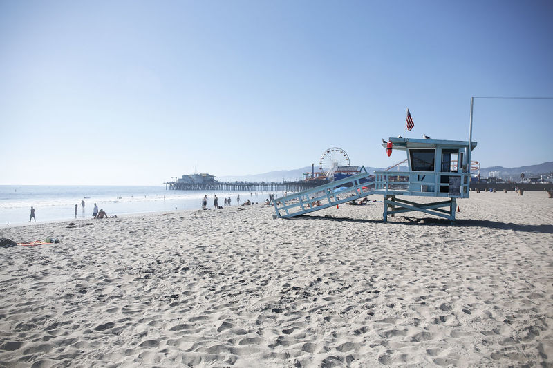 lifeguard hut in Santa Monica beach with the pier on background Beach Beauty In Nature Clear Sky Coast Day Emergency Ferris Wheel Lifeguard  Lifeguard Hut Nature No People Oil Pump Outdoors Pier Roller Coaster Sand Santa Monica Beach Santa Monica Pier Sea Sky Summer Sunlight USA Water Live For The Story