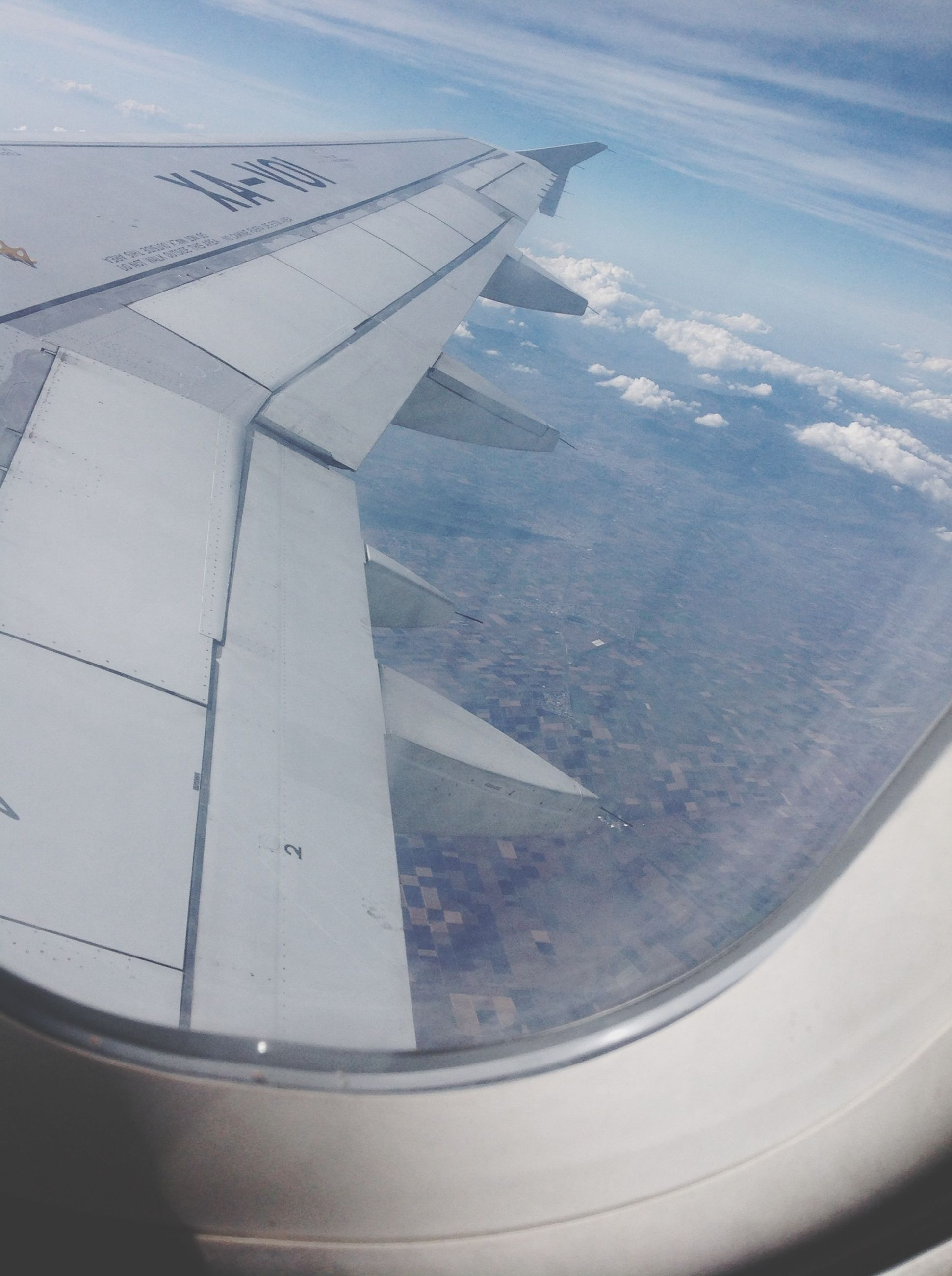 airplane, air vehicle, aircraft wing, transportation, mode of transport, flying, aerial view, part of, cropped, travel, mid-air, journey, public transportation, on the move, sky, landscape, aeroplane, airplane wing, vehicle part, aircraft