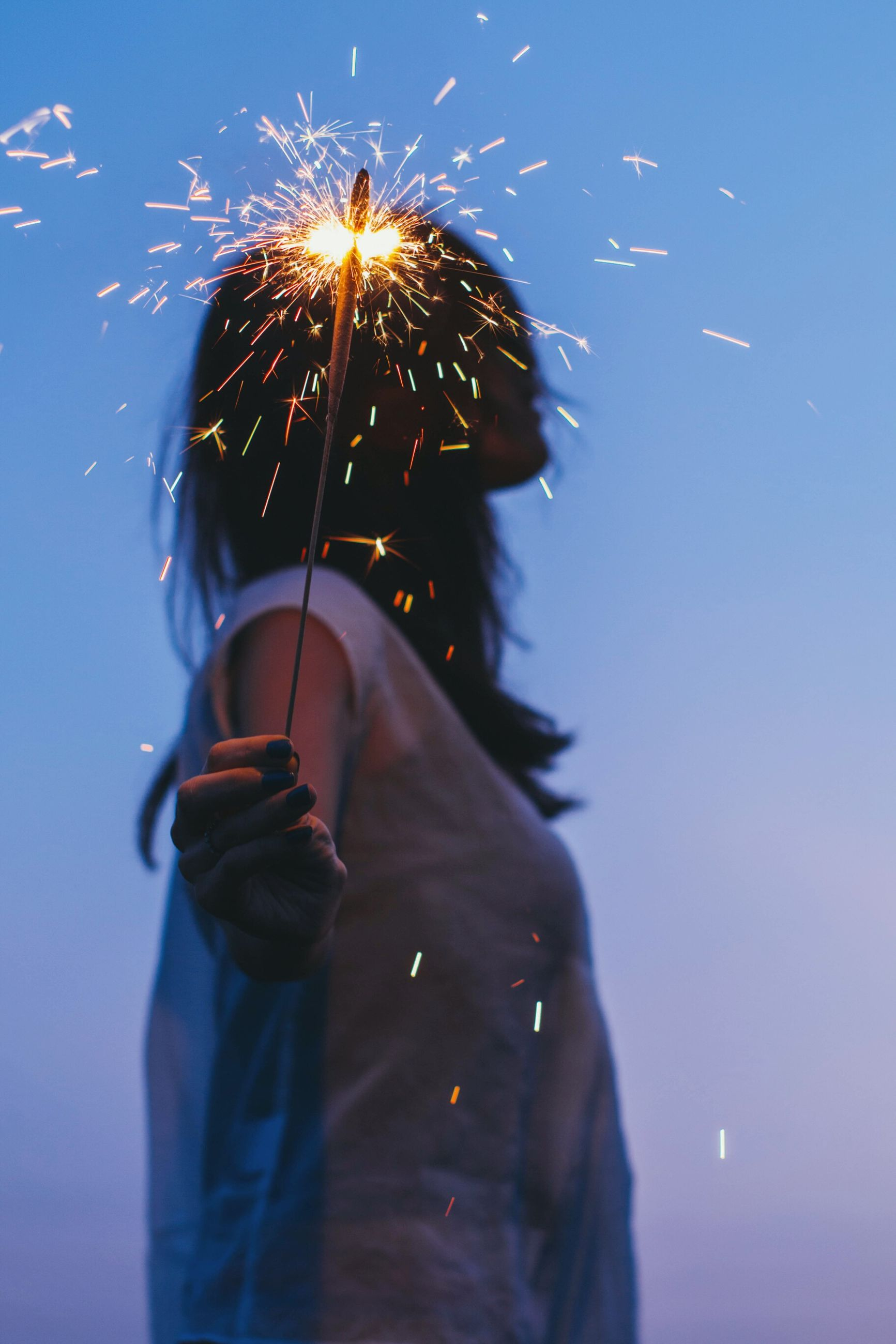 real people, one person, celebration, sparkler, outdoors, leisure activity, lifestyles, sky, firework display, low angle view, standing, clear sky, men, women, day, nature, close-up, people