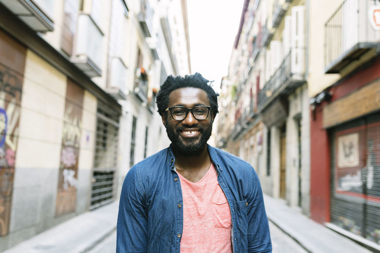 Portrait of a handsome young african man in the street. African Afro American City Cool Lifestyle Man Attractive Black Dreadlocks Hairstyle Handsome Hipster Male Mobilephone Outdoors People Portrait RASTA Smartphone Street Sunglasses Texting Trendy Urban