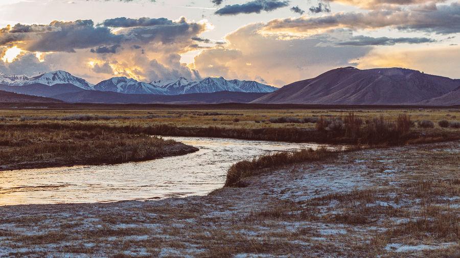 Owens river runs though arid plains against sierra nevada mountains and dramatic sunset sky