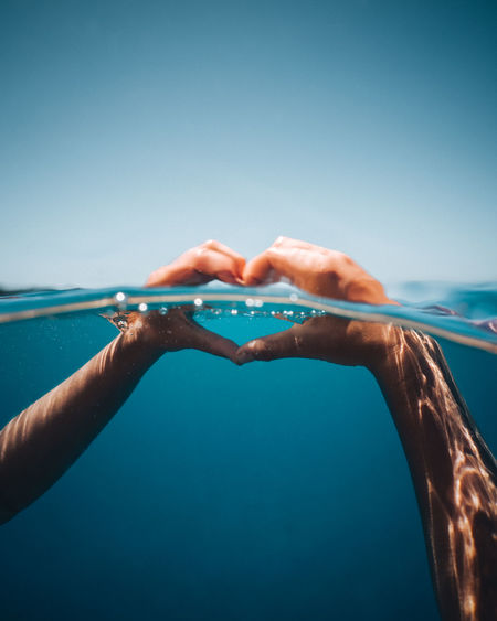 Close-up of hands making heart shape in sea against clear sky