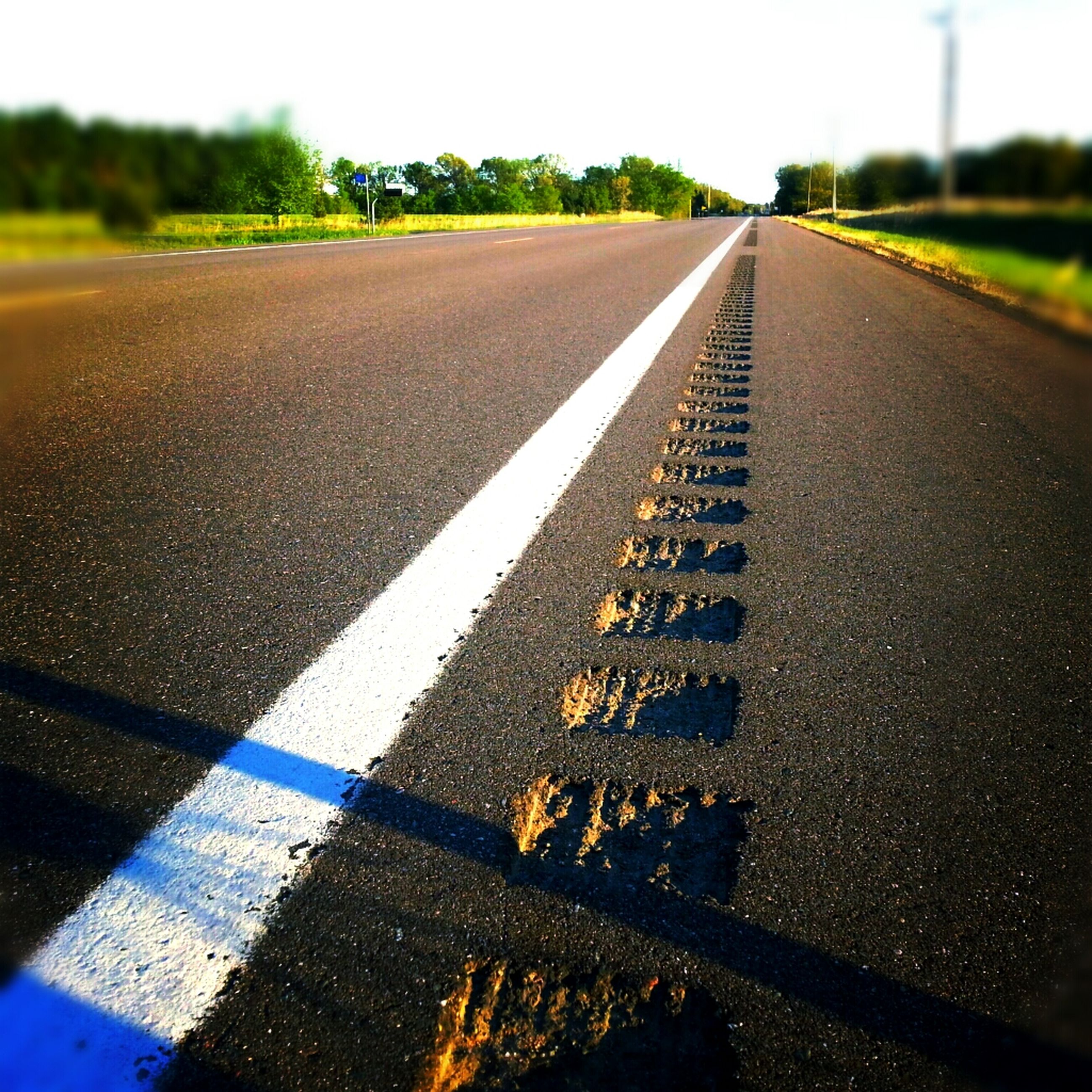road marking, the way forward, transportation, asphalt, diminishing perspective, road, vanishing point, surface level, street, empty, empty road, day, no people, outdoors, dividing line, close-up, direction, long, sunlight, sky