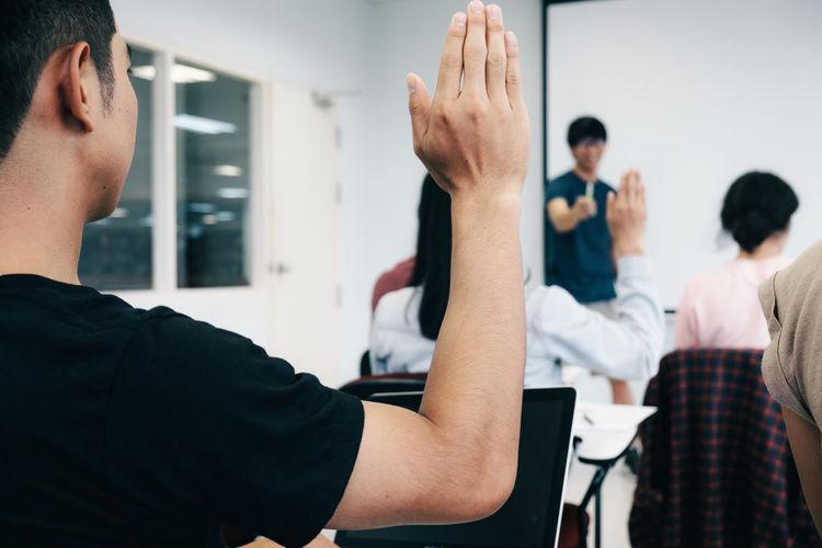 Close-Up Of Man Raising Hand In Classroom