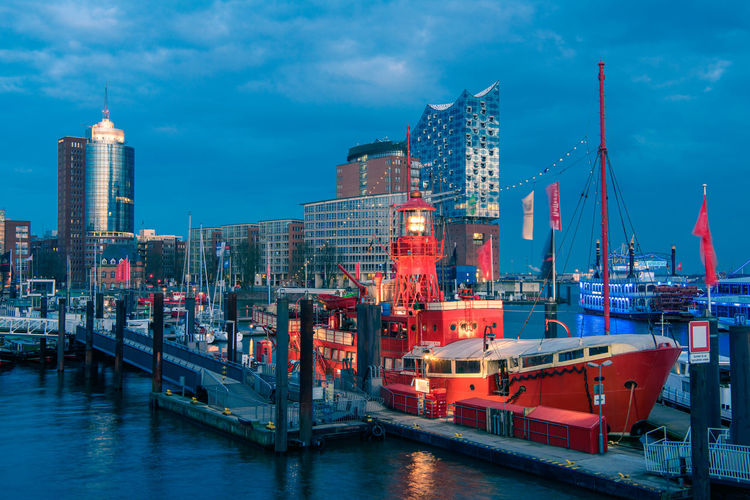 HAMBURG, GERMANY - MARCH 27, 2016: The red fire patrol boat in the marina of Hamburg with its restaurant waits for guests who want to enjoy dining in a maritime environment. Hamburg Harbor Red Ship Blue Hour Sky Water Illuminated Cloud - Sky Architecture Building Exterior No People Nautical Vessel Built Structure Transportation Nature Waterfront City Outdoors Cityscape Skyscraper