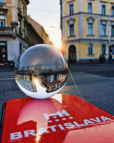 Close-up of crystal ball on street against building in city