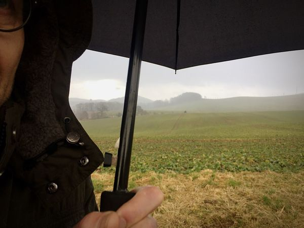 Real People Field Agriculture One Person Landscape Lifestyles Leisure Activity Men Outdoors Day Nature Human Hand Umbrella Rain Walking Hiking
