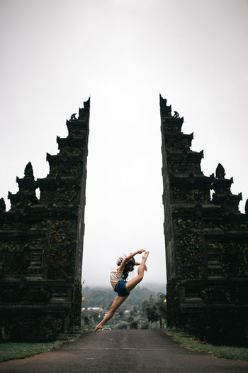 Low Angle View Of Woman Dancing In Entrance Against Sky