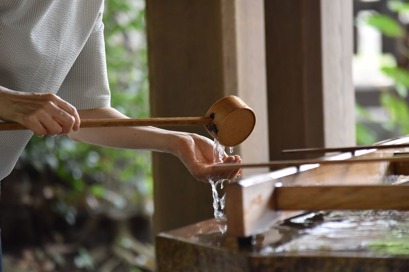 Midsection Of Woman Washing Hand With Water In Shrine