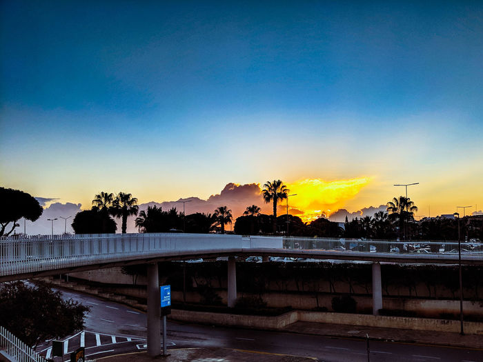 Bridge over road against blue sky during sunset
