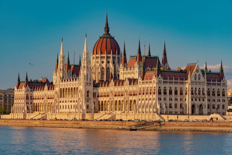 Hungarian Parliament Building By River Against Blue Sky
