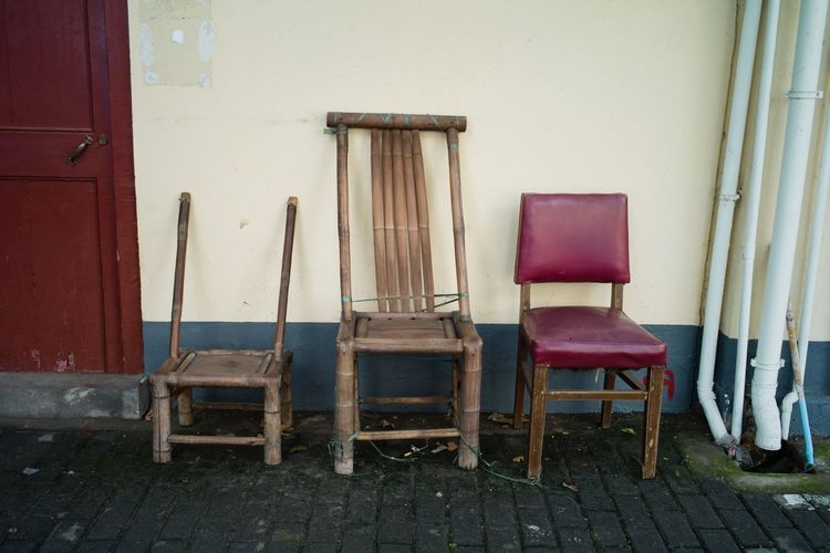 Empty chairs and tables against wall in old building
