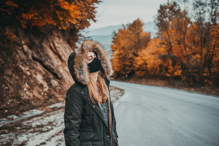 Woman with mask standing on the road during autumn