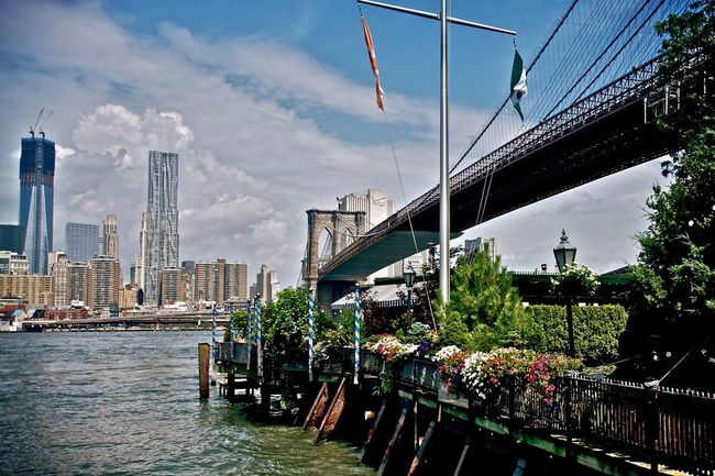 City Architecture Building Exterior Urban Skyline Skyscraper Modern Travel Built Structure Growth Travel Destinations Sky City Life Development Outdoors Cityscape Cloud - Sky Iconic Landmark Brooklyn Bridge / New York Water Waterfront Scenics Nautical Vessel Day No People