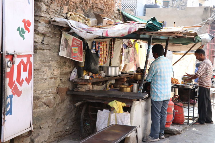 Rear view of people working at market stall