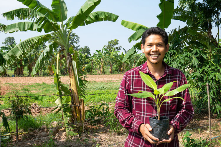 Portrait of Asian farmer smiling in corn field, Thailand Man Farmer Asian  Plant Banana Cultivation Agriculture Field Thai Adult Smile Happy Portrait Handsome People person One Young Male Tropical Thailand Pot Outdoor ASIA Plantation Farm One Person Looking At Camera Front View Smiling Growth Young Adult Nature Young Men Happiness Day Outdoors