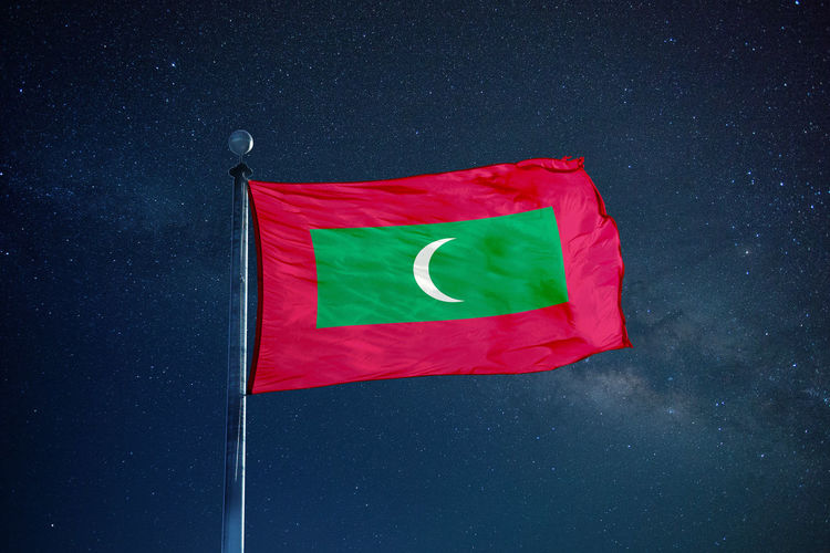 Low angle view of maldives flag against star field sky