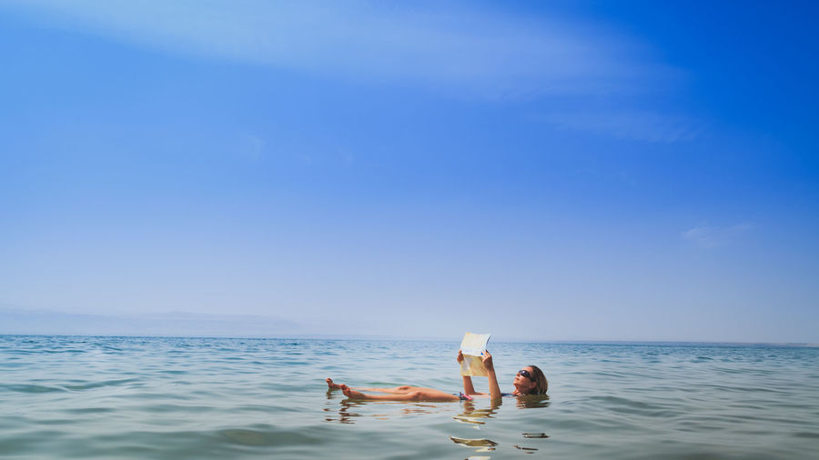 SCENIC View Of Woman Floating In The Red Sea While Reading