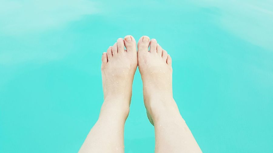Low section of woman against swimming pool