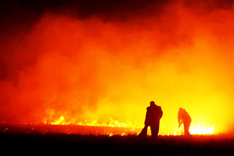 Silhouette Firefighters Working On Burning Gassy Field