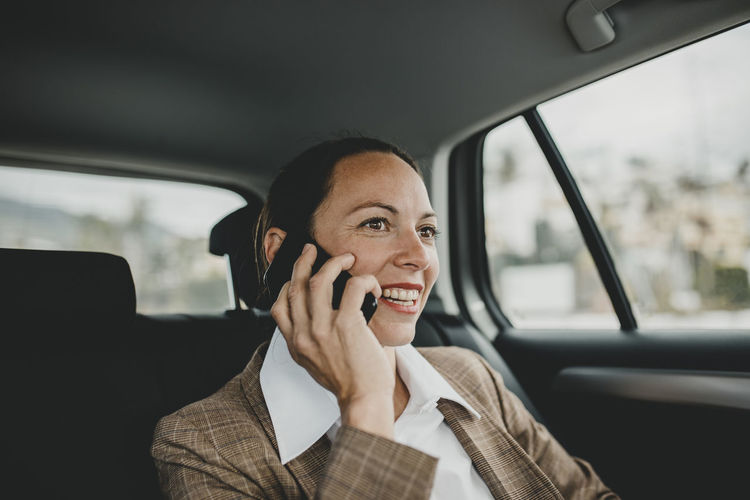 Portrait of smiling woman sitting in car