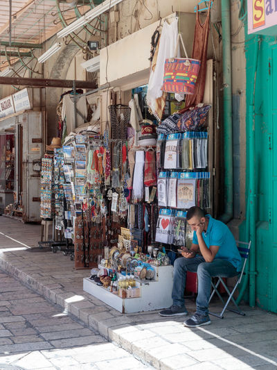 Jerusalem, Israel, July 14, 2017 : The seller is sitting near the souvenir shop in the Muristan Street in the old city of Jerusalem, Israel. Ancient Bazaar Business City Famous Market Sale Tradition Travel Adult Day Gift History Israel Jerusalem Muristan Old One Person Seller Shop Sitting Souvenir Street Tourism Traditional
