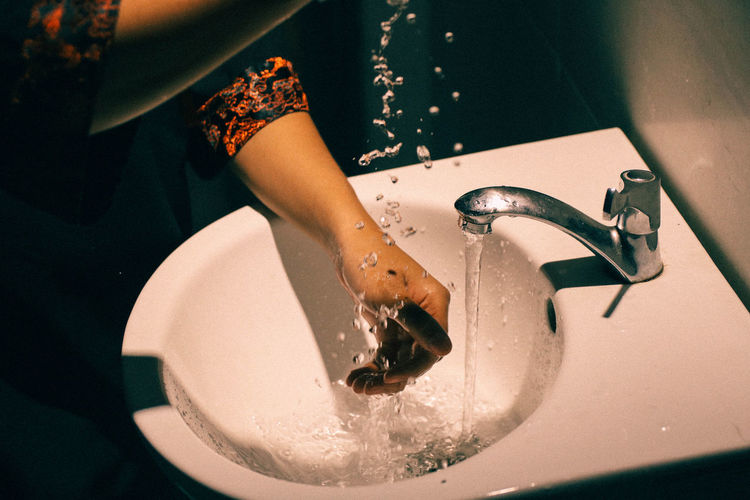 Cropped image of woman washing hands in sink