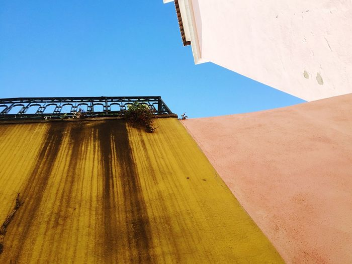 Low angle view of stained wall of house against blue sky