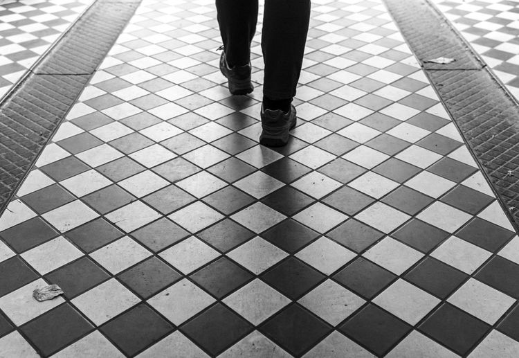 Low section of man walking on checked floor