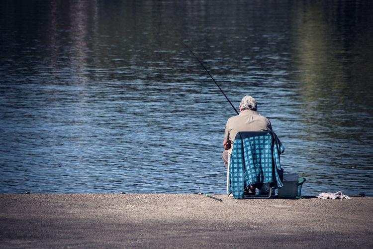 Rear view of senior man fishing in lake