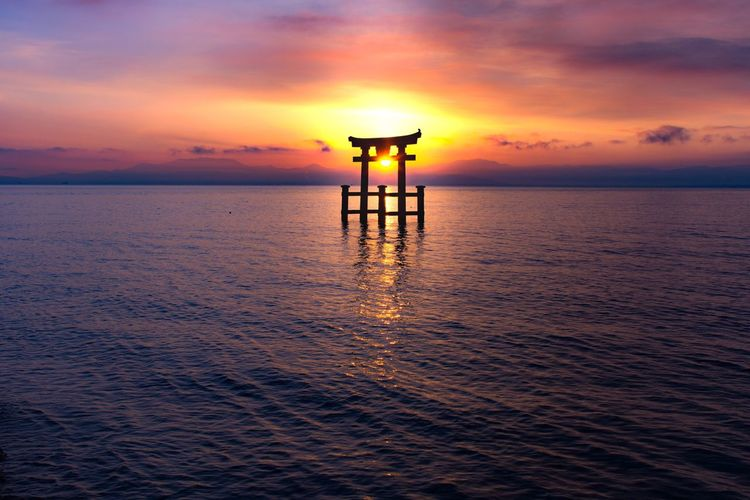 """"""" A day starting """" Sunset Water Nikonphotography Orange Color Beauty In Nature Horizon Over Water Built Structure Nature Tranquility Tranquil Scene Cloud - Sky No People Waterfront Architecture Scenics EyeEm Nature Lover Sun_collection Day Japan Japanese Shrine Lake Japan Photography Nikon Nikon D7200 EyeEmNewHere"""