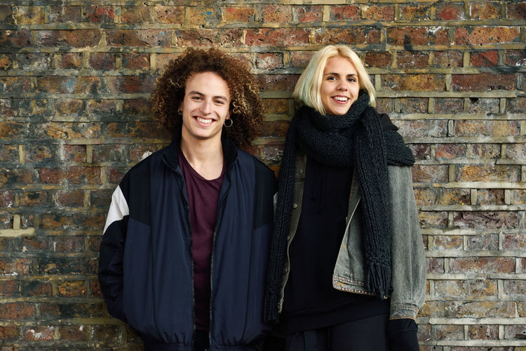 Portrait of smiling young couple against brick wall
