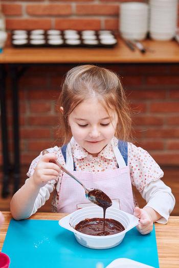 Girl making cake in classroom