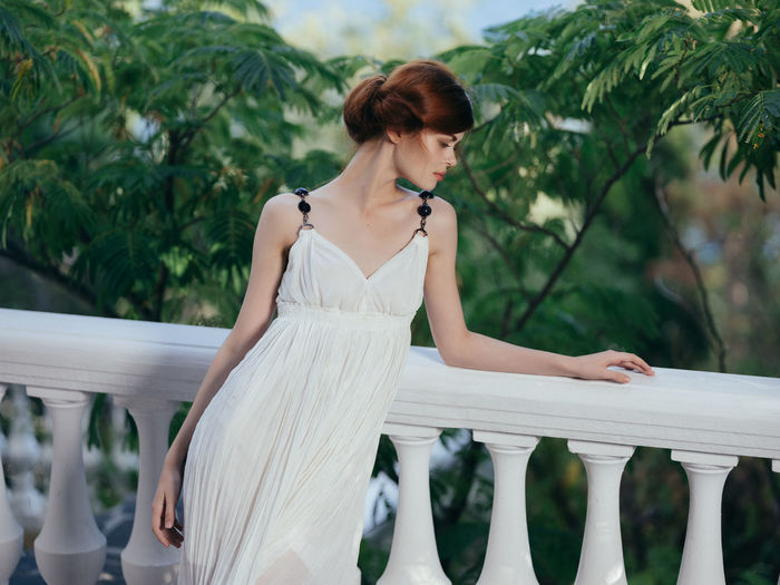 Beautiful woman standing by railing