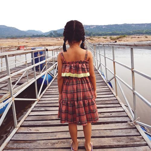 Rear view of girl standing on pier over lake against sky