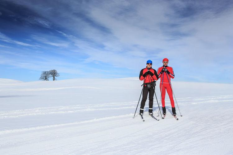 People skiing on snowy field against sky