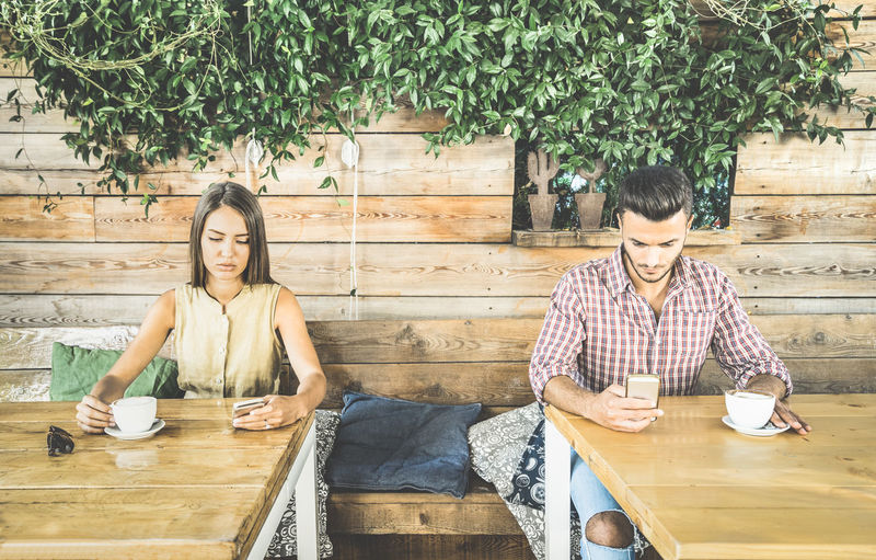 Couple Using Phones While Having Coffee In Cafe