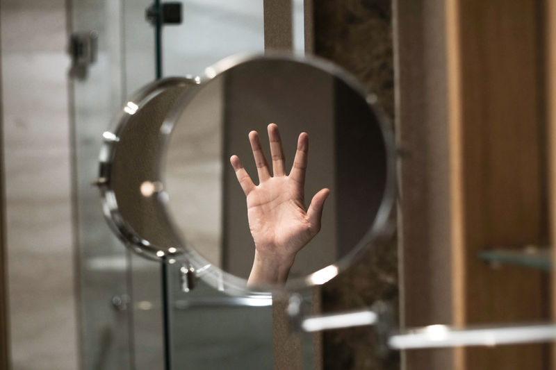 Midsection of person hand on mirror