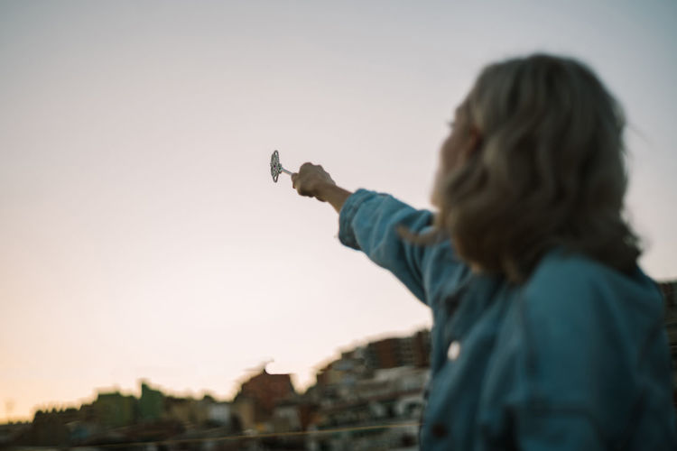 Midsection of woman holding umbrella against sky during sunset