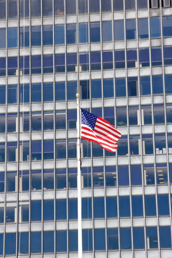 Low Angle View Of American Flag Against Modern Building