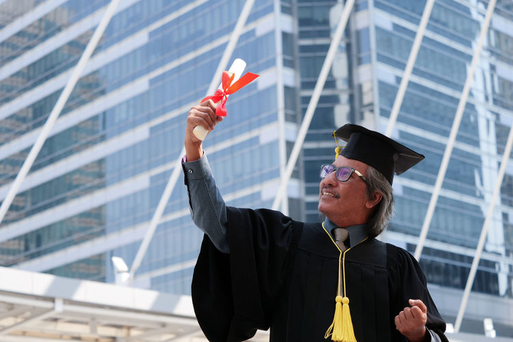 Businessman in graduation gown clenching fists against office building