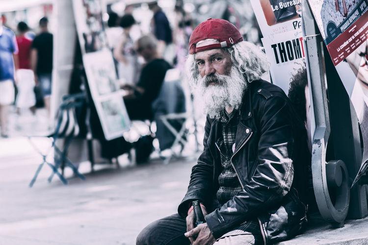 Portrait of man wearing hat sitting on street in city