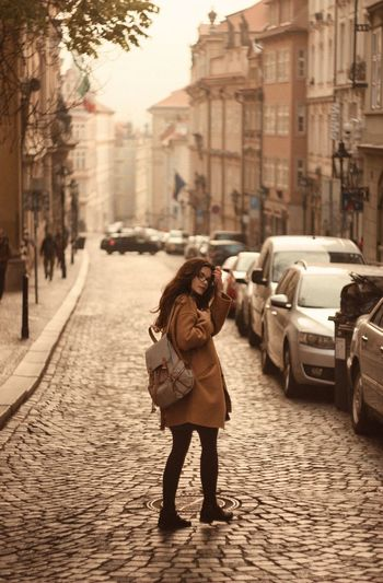 Side View Of Young Woman With Backpack Standing On Street In City