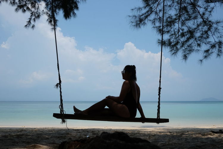 Silhouette woman sitting on swing at beach against sky