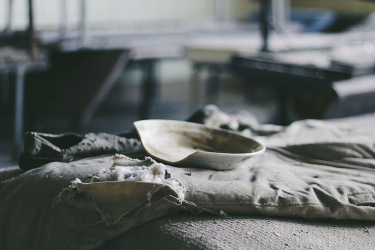 Close-Up Of Broken Plate With Old Pillow On Table