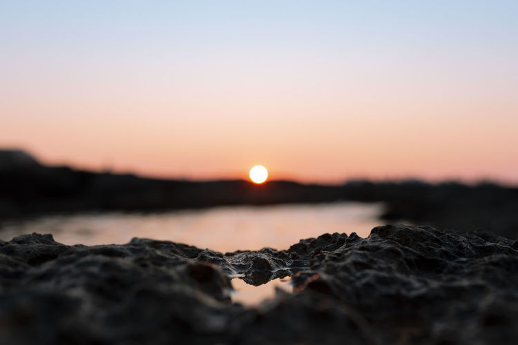 Surface level of rocks against sea during sunset