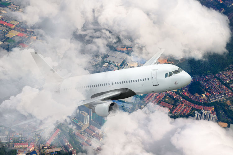 Plane flying sky. airplane above city. white passenger aircraft climbs through the clouds.